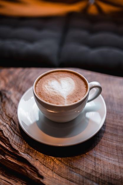 Tazza di cappuccino con un cuore sopra sul tavolo Foto Gratuite