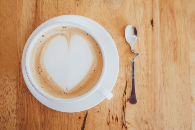 Чашка капучино с кремом в форме сердца Premium Фотографии