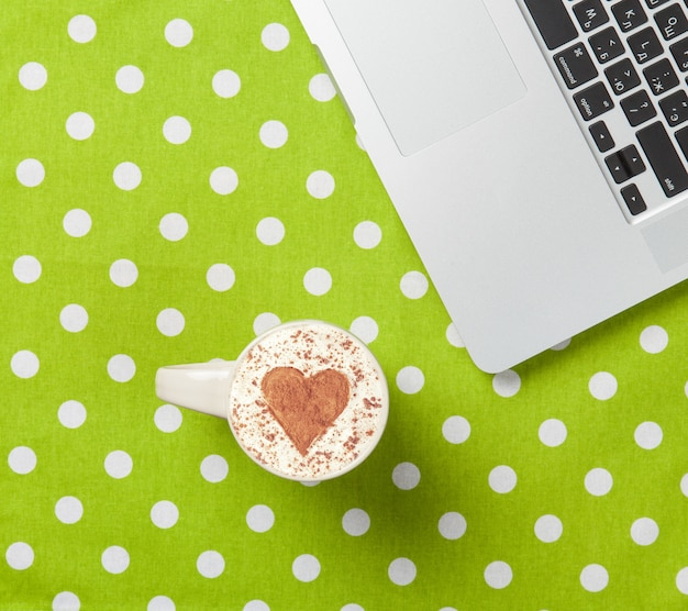 Cup of cappuccino with heart shape and laptop Premium Photo