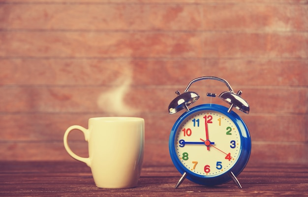 Cup of coffee and alarm clock on wooden table. Premium Photo