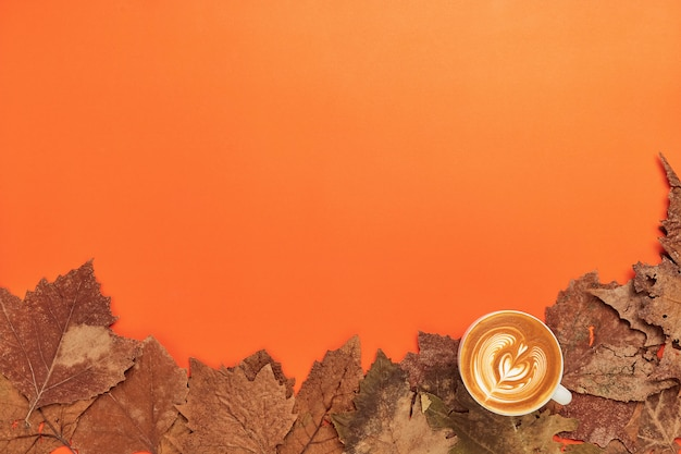 Чашка кофе и сухие листья на оранжевом фоне Premium Фотографии