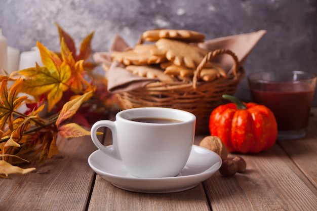 Cup of coffee, autumn leaves, cookies, pumpkin on the wooden table Premium Photo