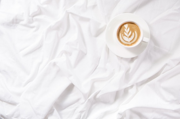 Cup of coffee in bed. morning flatlay in white bed. coffee and morning routine. Premium Photo