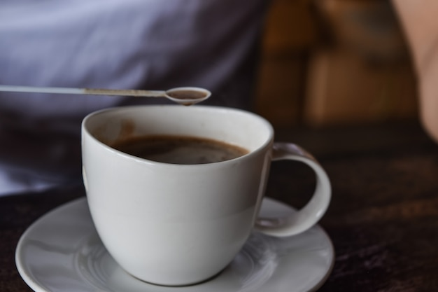 Cup of coffee being held by a male hand, while on wooden table top. Premium Photo