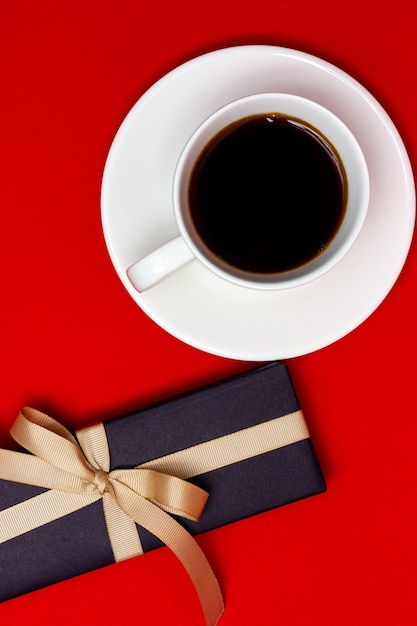 A cup of coffee and a black gift with a beige ribbon on a red background. view from above. Premium Photo