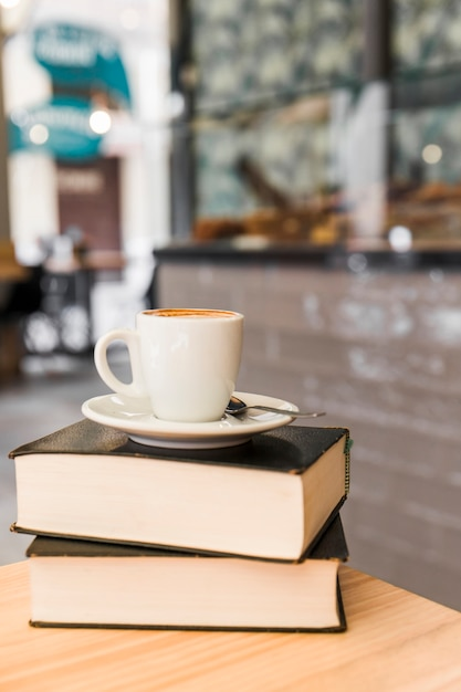 Cup of coffee over books on wooden table Free Photo