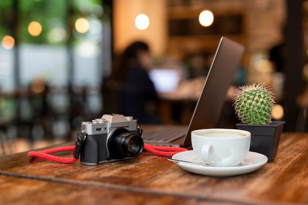 Cup of coffee and camera with  laptop on wooden table. Premium Photo
