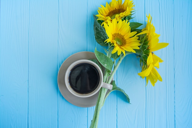 A cup of coffee cinnamon and sunflower on a blue background. Premium Photo