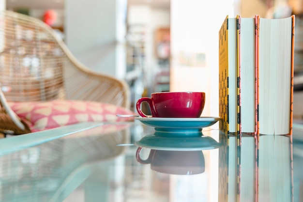Cup of coffee and closed book on reflective glass table Free Photo