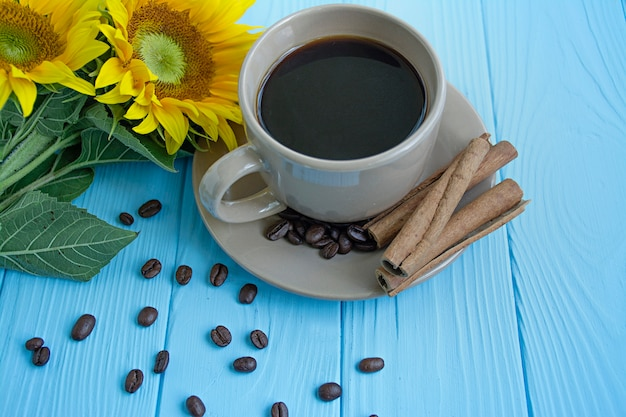 A cup of coffee, coffee beans, cinnamon and sunflower on a blue background. summer mood. Premium Photo
