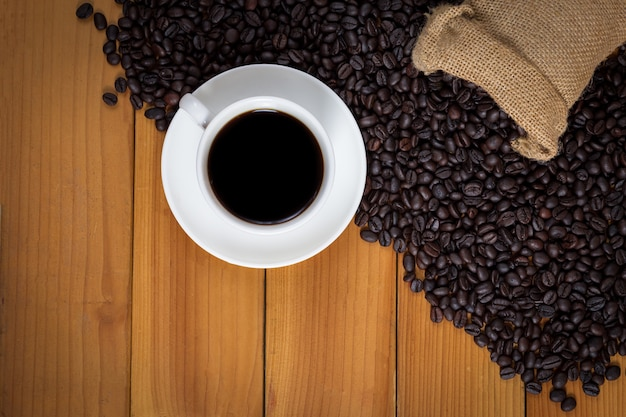 Cup of coffee and coffee beans in a sack on wood Premium Photo