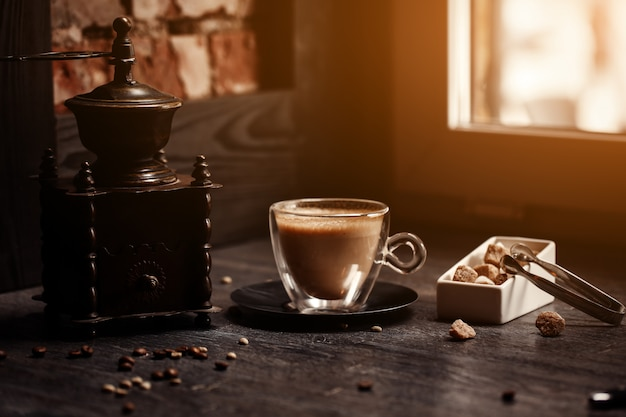Cup of coffee in coffee. grinder and cane sugar on table with flare blurred background. Premium Photo