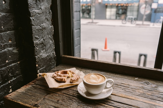Cup of coffee next to a cookie put on the windowsill Free Photo