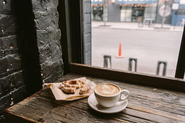 Tazza di caffè accanto a un biscotto messo sul davanzale della finestra Foto Gratuite