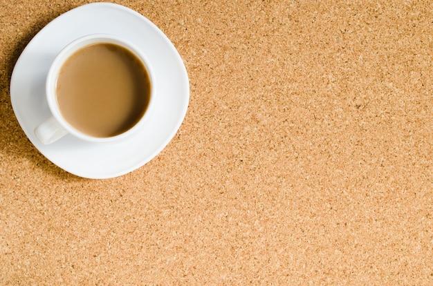 Cup of coffee on cork board. Premium Photo