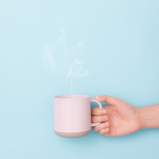 Cup of coffee in the hand on blue background Premium Photo