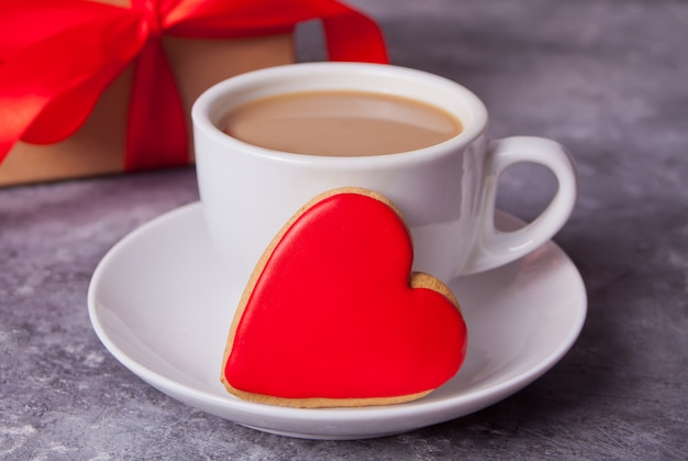 Cup of coffee and a heart shaped red cookie with gift box on the background. Premium Photo