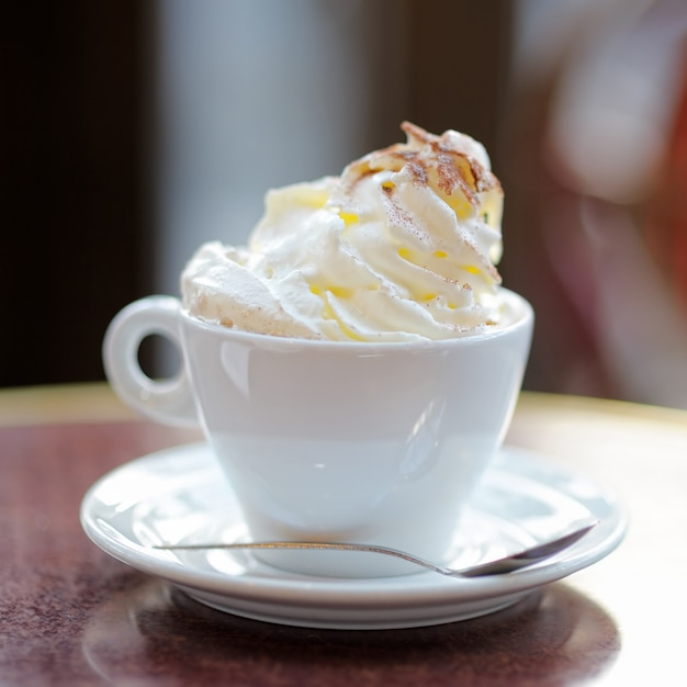 Cup of coffee or hot chocolate with whipped cream on the table at the cafe Premium Photo