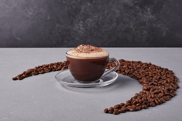 A cup of coffee in the mildde of arabica beans. Free Photo