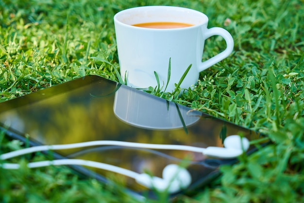 Cup of coffee next to a mobile with headphones Free Photo