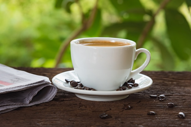 A cup of coffee and a newspaper Premium Photo