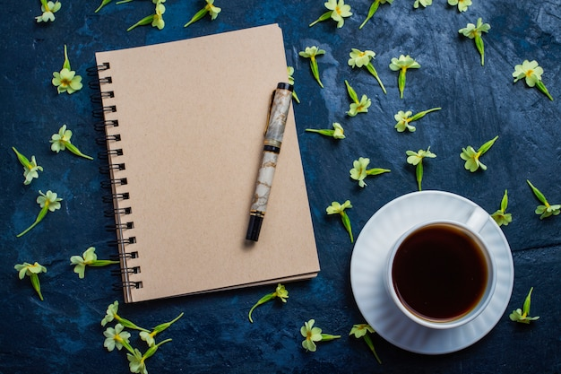 Cup of coffee, notebook and flowers on a dark blue background. flat, top view Premium Photo