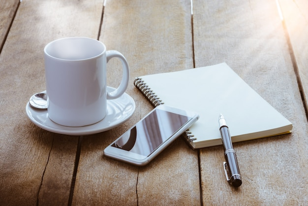 Cup of coffee, notebook, pen and smart phone Premium Photo