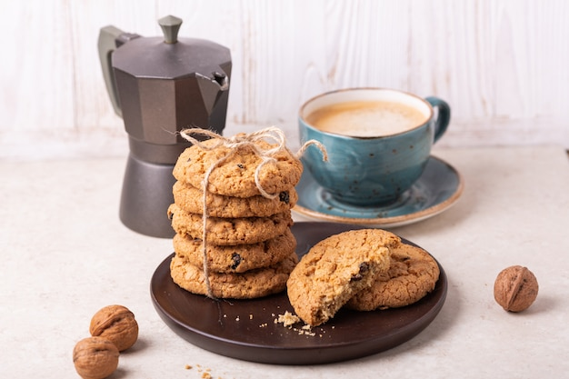 Cup of coffee, oatmeal cookies, coffee maker Premium Photo