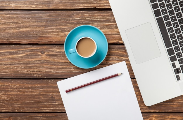 Cup of coffee and paper with laptop computer Premium Photo