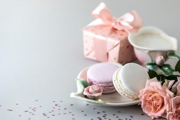 Tazza di caffè, pasta per la torta, un regalo in una scatola e rose rosa su sfondo grigio. copia spazio. Foto Gratuite