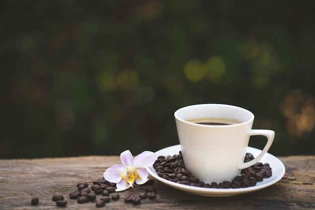 Чашка кофе, фалеанопсис на деревянный стол. Premium Фотографии
