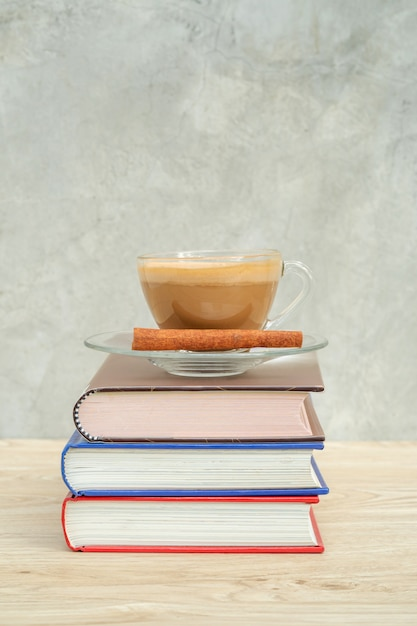 A Cup Of Coffee And A Pile Of A Book On A Wooden Table Photo
