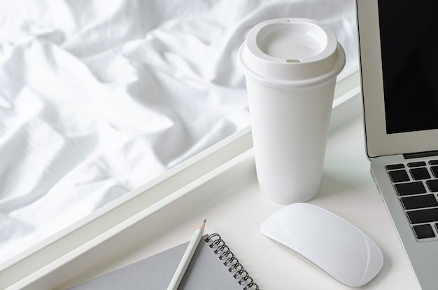 A cup of coffee puts beside laptop computer and mouse with white tray on messy blanket for working on bed. Premium Photo