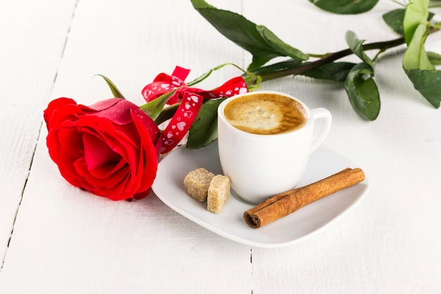 Cup of coffee, red rose, sugar and cinnamon on a white wooden background Premium Photo
