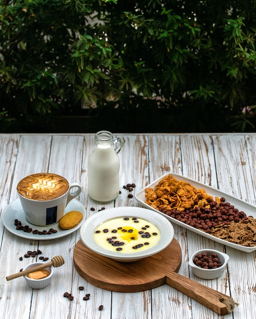 A cup of coffee served with milk and dessert Free Photo