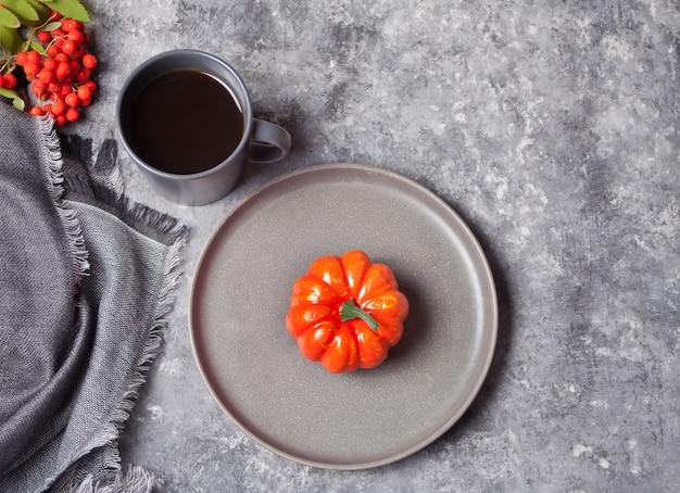 Cup of coffee, small pumpkin on the concrete Premium Photo
