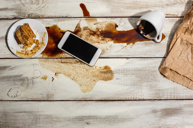 Cup of coffee spilled on wooden table Free Photo