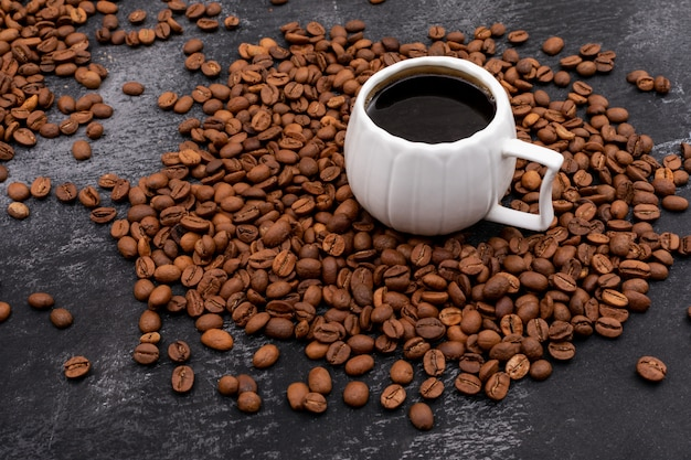 Cup of coffee surrounded with coffee beans on black surface Free Photo