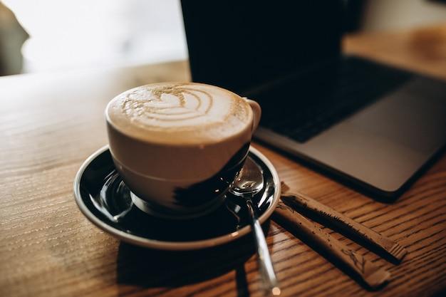 Tazza di caffè sul tavolo vicino al computer portatile Foto Gratuite