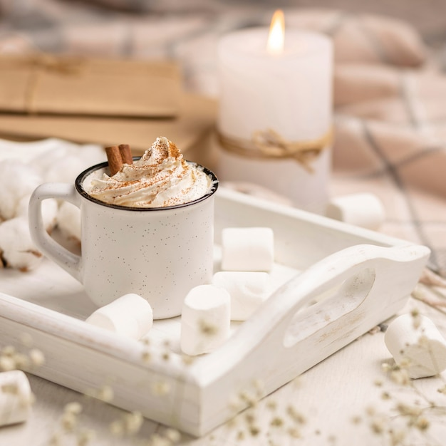 Cup of coffee on tray with whipped cream and candle Free Photo