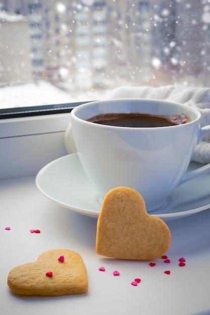 Cup of coffee on a winter windowsill. Premium Photo