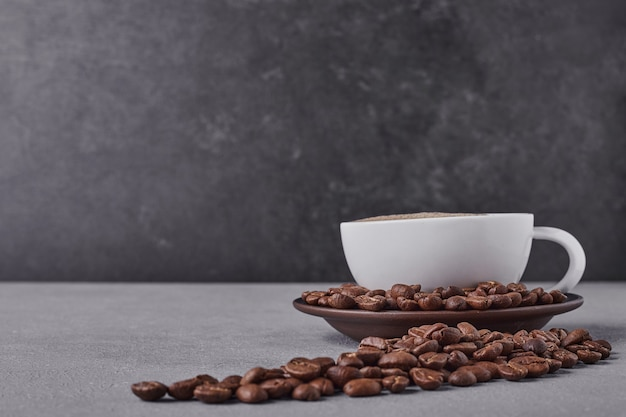 A cup of coffee with arabica beans around. Free Photo
