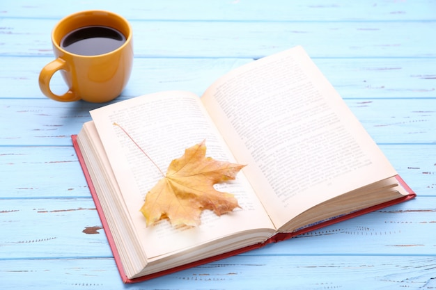 Cup of coffee with autumn leaf and book on wooden background Premium Photo
