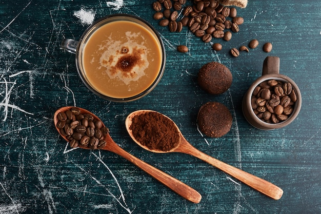 A cup of coffee with beans and cookies around. Free Photo