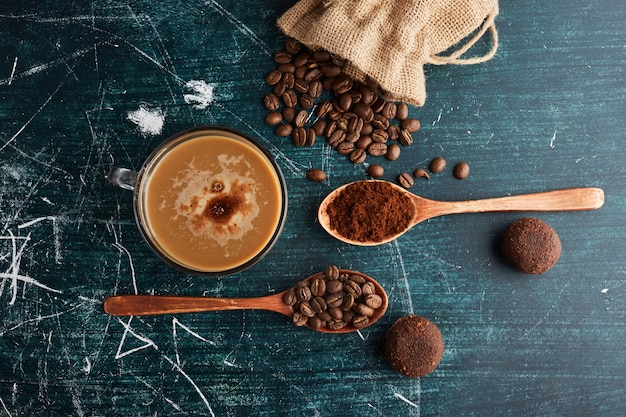 A cup of coffee with beans and cookies. Free Photo