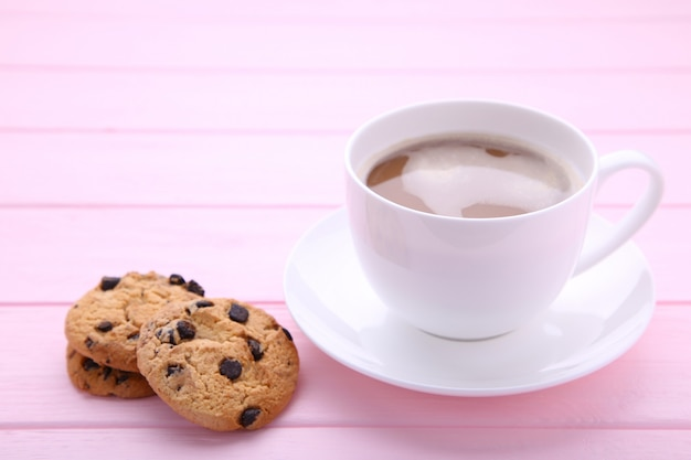 Cup of coffee with chocolate cookies on pink background Premium Photo