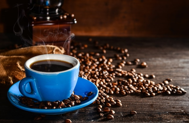 Cup of coffee with coffee beans and grinder background Free Photo