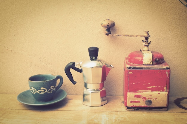Cup of coffee with a coffee pot and a grinder Free Photo
