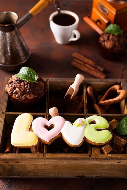 Cup of coffee with cooffee beans, wooden box with grains of coffee and spices, cookies Premium Photo