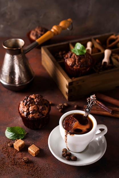 Cup of coffee with cooffee beans, wooden box with grains of coffee and spices, cupcake Premium Photo